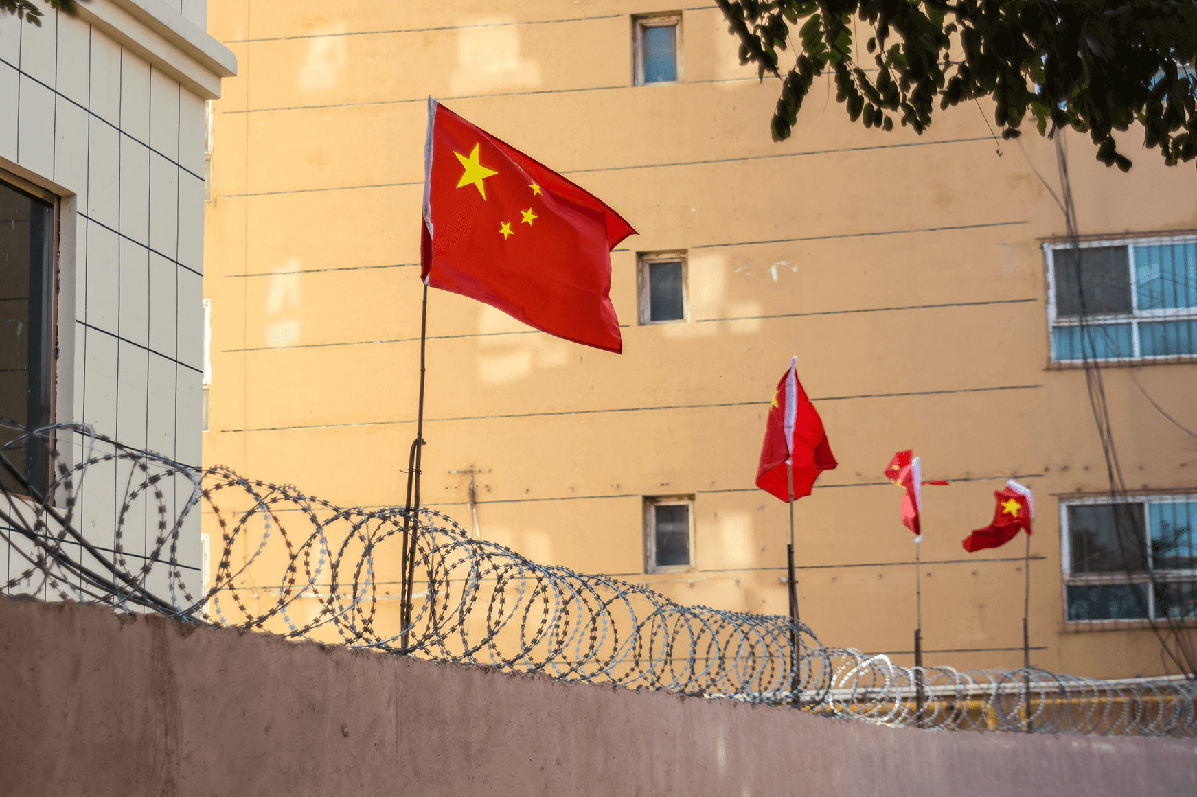 Flag of China above wall with razor wire